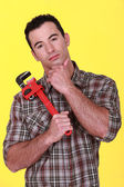 Workman holding a pipe wrench — Stock Photo