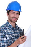 Foreman holding radio and plans — Stock Photo