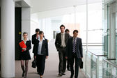 Businesspeople walking in a hallway — Stock Photo