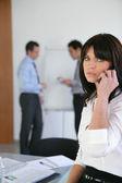 Jonge vrouw op een telefoon tijdens een vergadering van het bureau — Stockfoto