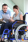 Disabled female office worked with colleague — Stock Photo