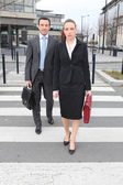 Businessman and woman crossing the street — Stock Photo