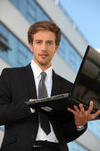 Man in suit carrying a laptop — Stock Photo