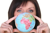 Woman showing a globe — Stock Photo