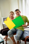 Couple sat at home holding colorful posters — Stock Photo