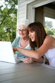 Elderly woman and girl with computer — Stock Photo