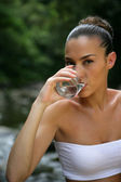 Woman drinking a glass of water by a river — Stock Photo