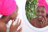 Woman looking in mirror — Stock Photo