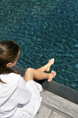 Woman sat on decking in white bathing robe — Stock Photo