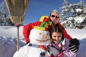 Padre e figlia con pupazzo di neve — Foto Stock