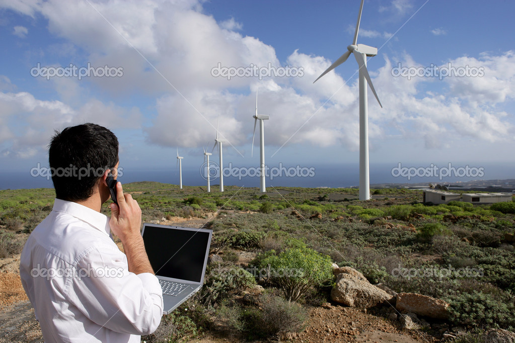 Young businessman on phone next to wind turbines  Stock Photo #8456307