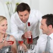 Man serving rose wine at a dinner party - Stockfoto