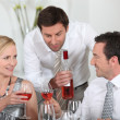 Stock Photo: Mserving rose wine at dinner party