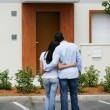 Couple standing in front of their dream home - Stock Photo