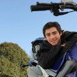 Adolescent boy posing with his motorcycle - Stock Photo