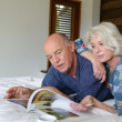 Senior couple looking at a magazine in bed — Stock Photo #8462949