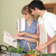 Stock Photo: Couple following recipe book