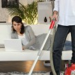 Royalty-Free Stock Photo: Man vacuuming and woman laid with laptop