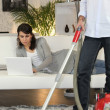 Man vacuuming and woman laid with laptop - Stock Photo