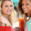 Two 20 years old girls, a blonde and a metis doing shopping — Stock Photo