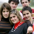 Group of teenagers gathered in local park - Stock Photo