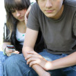Teenage couple texting on their cellphones — Stock Photo #8466794