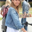 Smiling teenage girl with bicycle — Stock Photo