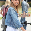 Smiling teenage girl with bicycle — Stock fotografie