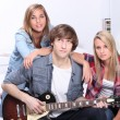 Teenager with guitar sat with friends - Stock Photo