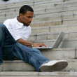 Black man working on laptop in stairs - Stock Photo