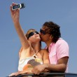 Funky couple in a convertible taking a photo on a cellphone — Stock Photo #8469155