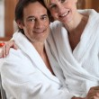 Stock Photo: Womin bathrobe, sitting on her partner's lap