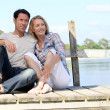 Couple sat on jetty — Stock Photo