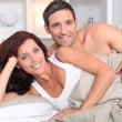 A couple reposing in bed in the morning — Stockfoto
