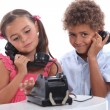 Little boy and girl with old fashioned telephone — Stock Photo