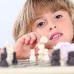 Cute blond girl playing chess — Stock Photo