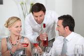 Hombre sirviendo vino en una cena rosado — Foto de Stock