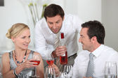 Man serving rose wine at a dinner party — Stock Photo