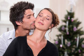 Man kissing his partner in front of a Christmas tree — Stock Photo