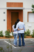 Couple standing in front of their dream home — Stock Photo