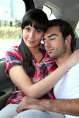 Tired couple in the back of a car — Stock Photo