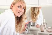 Młoda blond kobieta ubrana w szlafrok w łazience — Zdjęcie stockowe
