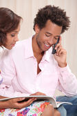 Young man at phone and his girlfriend — Stock Photo