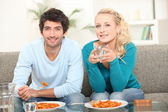 Young couple having meal at home — Stock Photo