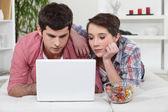 Mladý pár s notebookem doma — Stock fotografie