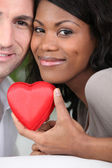 Loving couple holding a heart case — Stock Photo