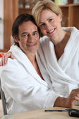 Woman in a bathrobe, sitting on her partner's lap — Stock Photo