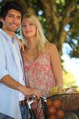 Summery couple with a basket of fruit — Stock Photo