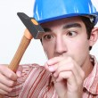 Builder hitting nail with hammer - Stock Photo