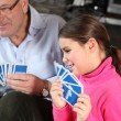 Stock Photo: Little girl playing cards with grandfather